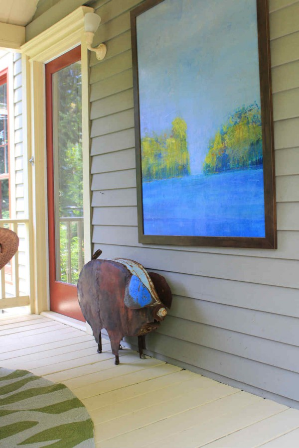 Collected antique and art grace the inviting porch of a Virginia river retreat. </br>(Montross, Virginia)