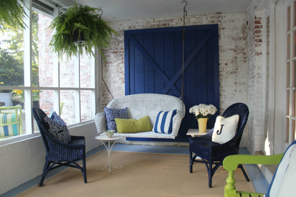 A custom-built barn door contributes to the southern charm on a screened porch. </br>(Arlington, Virginia)