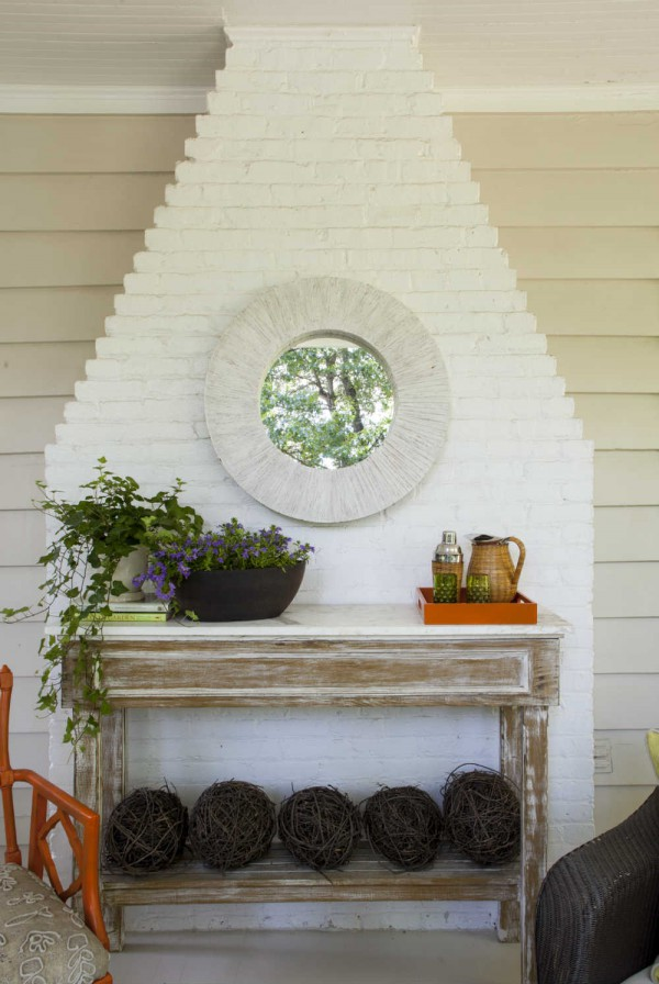 A hand crafted console table and yard-reflecting mirror accent the brick chimney on this suburban porch. </br>(Arlington, Virginia)